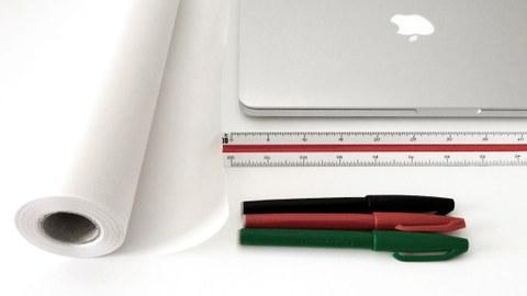 Foto eines Laptops, Lineals, Stiften und einer Pergamentrolle