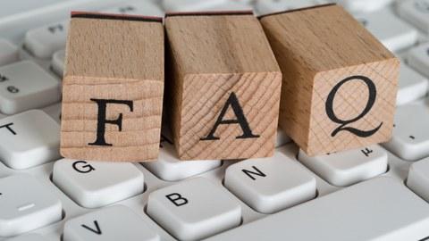 Das Foto zeigt drei Holzwürfel auf einer Tastatur. Auf den Holzwürfeln sind die Buchstaben FAQ abgebildet.