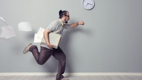 Mann rennt mit Zetteln unterm Arm mit Blick auf die Uhr