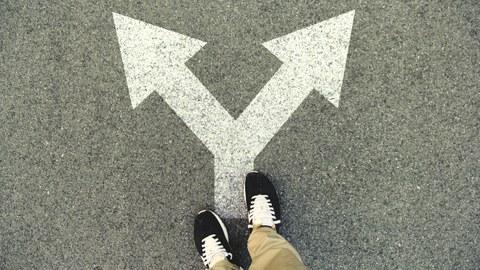 Füße stehen auf einem auf Asphalt gemalten Pfeil, der nach rechts und links zeigt