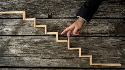 Geschäftsmann oder Student geht mit den Fingern hölzerne Stufen hinauf