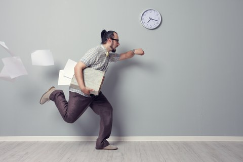 In the photo you see a man. He runs and loses a lot of papers. The man looks at his watch and runs past a wall on which another watch is hanging.