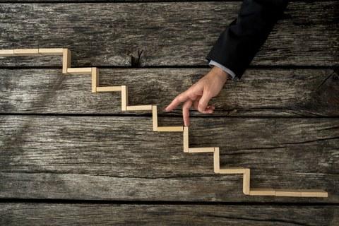Das Foto zeigt einen Arm vor einem hölzernen Hintergrund. Darauf liegen Holzstückchen, die eine Treppe bilden. Die Person geht mit ihren Fingern die Treppe hinauf.