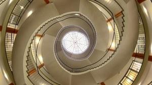 Treppenaufgang im Hülße-Bau der TU Dresden. Das Bild wurde von unten aufgenommen. Den Mittelpunkt bildet das Dachfenster, dessen Konstruktion wie ein Spinnennetz aussieht. Von unten betrachtet läuft die Treppe spiralförmig nach oben.
