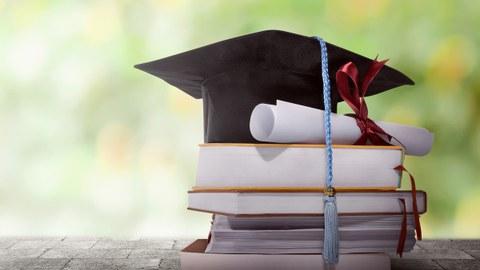 Graduation Hut mit Grad Papier auf einem Stapel Bücher