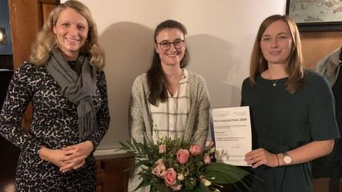 Die Preisträgerin des Lewicki-Preises (Frau Sabrina May) mit Blumenstrauß und Urkunde, links davon Frau Dr. Anne Harzdorf, rechts davon Frau Romy Adam.