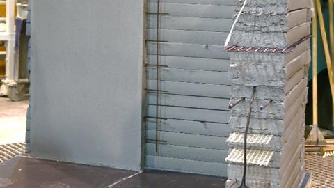 Dargestellt ist eine Wand aus mehreren aufeinandergestapelten Betonschichten, die durch einen Drucker aufgetragen wurden. Zwischen den Schichten befinden sich verschiedene eingelegte Bewehrungsstrukturen.