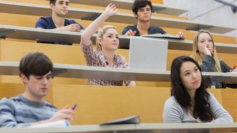 Eine Studentin sitzt in einem Hörsaal und meldet sich.