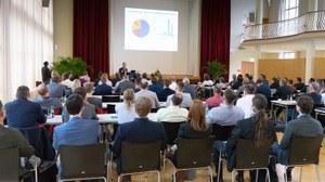Teilnehmer, die den Vortragenden in einem Konferenzsaal zuhören.