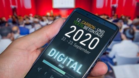 Foto zeigt eine Hand mit einem Smartphone und eingeblendetem Texthinweis, dass die 12. Carbon- und Textilbetontage 2020 nur digital stattfinden. Im Hintergrund ist eine unscharfe Konferenzsituation zu sehen.