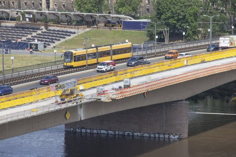 Photo shows a section of the Carola Bridge during the renovation. Several cars and a tram crosses the bridge.