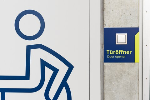 Rollstuhlsymbol auf einer Tür im Hörsaalzentrum. Rechts davon der Schalter eines Türöffners.