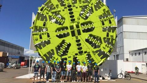 """Gruppenfoto vor einer Tunnelbohrmaschine des Herstellers """"Herrenknecht"""" mit einem Durchmesser von fast dem Sechsfachen der Länge eines Menschen"""