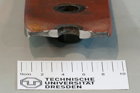 Brittle crack on the edge of a punched rivet hole, embrittlement due to strain ageing