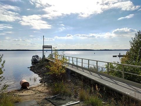 Blick auf die Wind- und Wellenmessstation Senftenberger See. Im Vordergrund befindet sich der Steg mit angebrachter Sensorik. Im Hintergrund ist der Senftenberger See bei sonnigem Wetter zu sehen.
