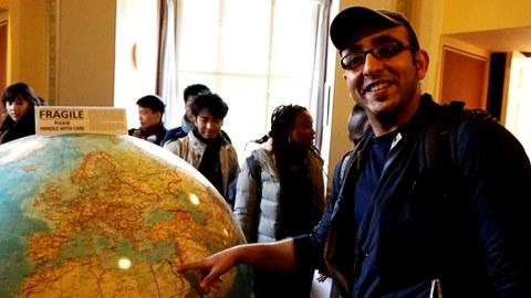 """Humbodt Stipendiat vor einem großen Globus mit der Aufschrift """"Zerbrechlich, bitte vorsichtig behandeln"""""""