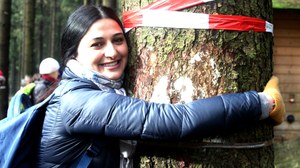 A participant is hugging a tree during an excursion