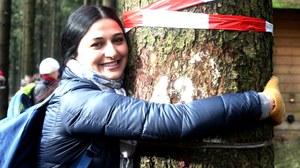 Teilnehmerin umarmt einen Baum auf einer Exkursion
