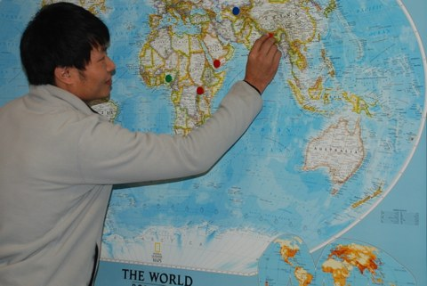 Participant marking his home country on a large world map