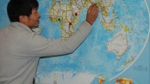 Ein Teilnehmer markiert sein Heimatland auf einer großen Weltkarte