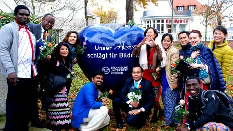 "Image showing a group of course participants posing next to a large heart with ""Our heart beats for education - TU Dresden"" written on it."