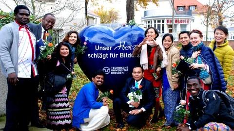 """Teilnehmer posieren neben einem großen Herz mit der Aufschrift """"Unser Herz schlägt für Bildung - TU Dresden"""""""