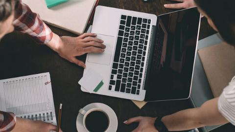 Draufsicht auf einen Tisch wo drei LEute arbeiten, mit Laptop, Notizen und Kaffe