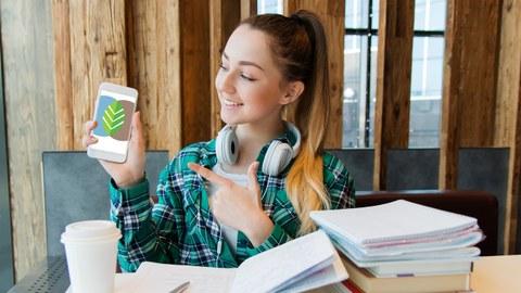 Frau, Studentin, Schreibtisch, Bücher, Handy im Hand, Frau zeigt auf ihren Handybildschirm