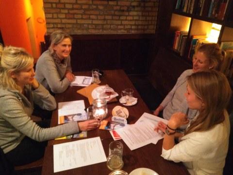 vier Frauen sitzen an einem Tisch und unterhalten sich freundlich