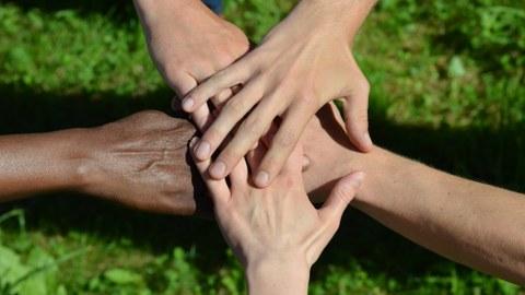 Hände, die sich berühren als Zeichen für Zusammenarbeit