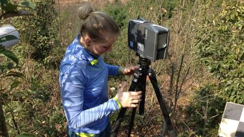 Eine Masterstudentin stellt einen Laserscanner im Gelände auf