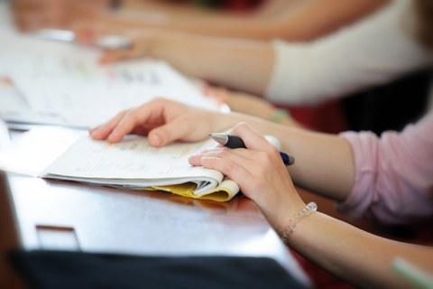 weibliche Hände auf einem aufgeschlagenen Hefter mit Vorlesungsunterlagen