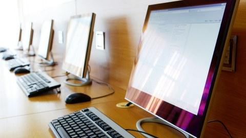 mehrere Computerbildschirme mit Tastaturen, aufgereiht auf einem langen Tisch vor einer Wand