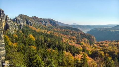 Vom linken Bildrand ziehen sich Sandsteinformationen (Schrammsteingrat) in die Bildmitte in Richtung Hintergrund. Der Vordergrund zeigt herbstlich gefärbten Wald und im rechten Drittel das etwas versteckte Elbtal mit einem Stück Elbe und steiler Talflanke