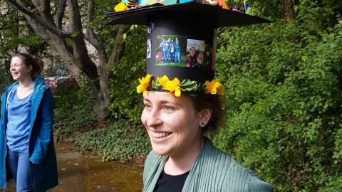 lachende Frau mit einem Doktorhut und einem Glas Sekt in der Hand steht in einem Park. Im Hintergrund steht eine weitere Person.