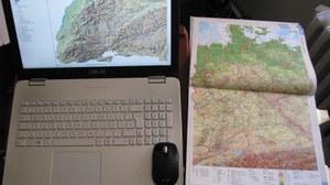 Das Bild zeigt eine Karte auf einem Notebook-Display und eine Atlaskarte