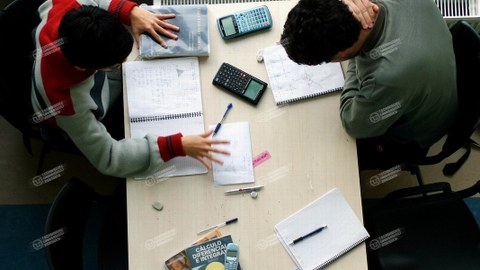 Zwei Studierende mit Taschenrechnern beugen sich über ihre Notizzettel.