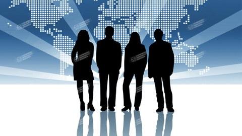 vier Menschen stehen vor einer Leuchtwand mit Weltkarte