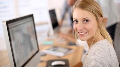 Das Foto zeigt eine junge Frau vor ihrem Computer. Sie hat sich gerade zur Seite gedreht und lächelt in die Kamera.