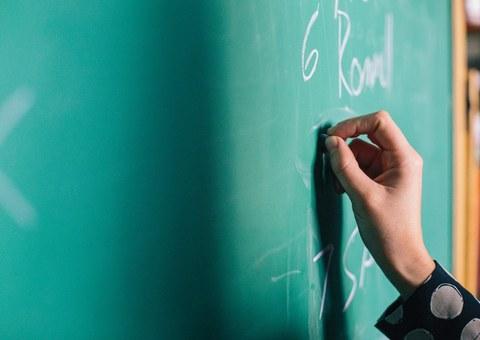 Lehrer schreibt an die Tafel