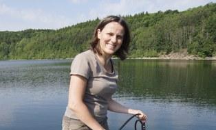 Lächelnde Person vor einem Standgewässer