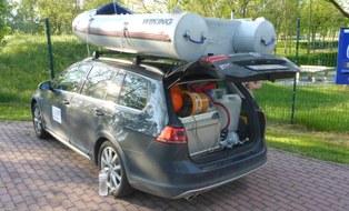 Auto mit vollbeladenem Kofferraum und Boot auf dem Dach