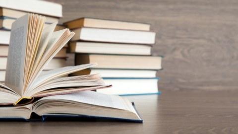 Auf dem Foto liegen zwei aufgeschlagene Bücher auf einem Tisch. Im Hintergrund ist ein Bücherstapel zu sehen.