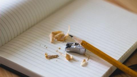 Gespitzter Bleistift liegt auf einem Heft