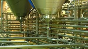 Fabrikhalle mit Behälter und Rohrleitungen aus Edelstahl