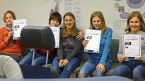 Schülerinnen zeigen ihre Zertifikate vom Bahnfahrsimulator