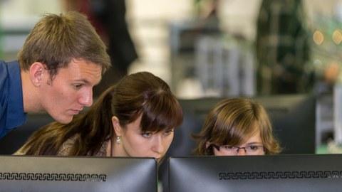 Zwei Studentinnen und ein Student schauen auf einen Bildschirm