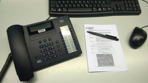 Telefon, Tastatur, Maus und Schreibblock liegen auf Schreibtisch.