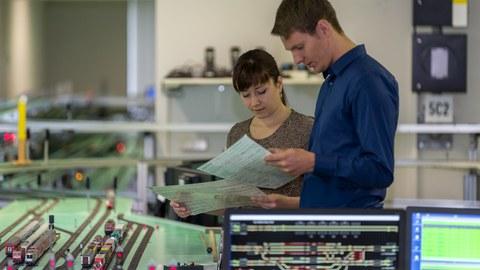Betreuerin und Student stehen im Labor und schauen auf Unterlagen.