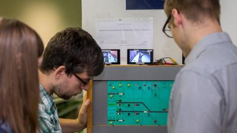 Betreuer erläutert zwei Studenten ein Stellwerk.